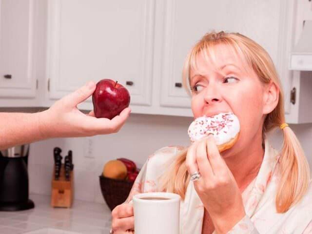 Женщина кушает пончик